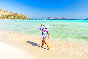 Beautiful woman with sun hat walking on idyllic empty beach, Crete, Greece