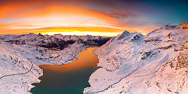 Aerial view of Lago Bianco and Bernina pass road crossing the snowcapped mountains at dawn, Graubunden, Engadin, Switzerland