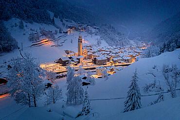 Winter dusk over the illuminated village in deep snow, Gerola Alta, Valgerola, Orobie Alps, Valtellina, Lombardy, Italy