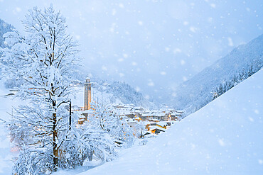 Snowflakes falling on mountain huts in the fairy tale alpine village at Christmas time, Valgerola, Valtellina, Lombardy, Italy