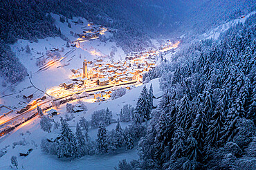 Trees covered with snow in the winter forest surrounding the alpine village at Christmas, Valgerola, Valtellina, Lombardy, Italy