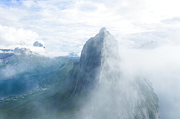 Aerial view of fog over the majestic Segla mountain peak emerging from clouds, Senja island, Troms county, Norway