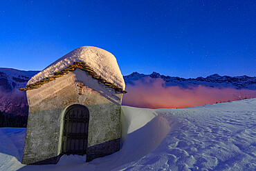 Small chapel covered with snow in the starry winter night, Andossi, Madesimo, Valchiavenna, Valtellina, Lombardy, Italy