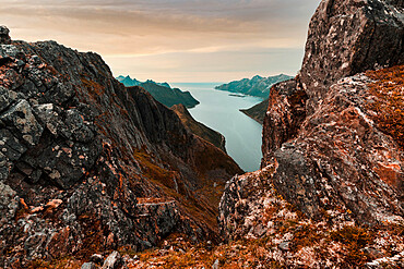Oyfjorden fjord view from steep hiking trail through red rocks of mountains, Senja island, Troms county, Norway
