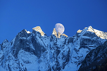 The moon appears behind the snowy mountains illuminating the peaks at sunset, Bondasca Valley, Swiss Alps, Switzerland, Europe