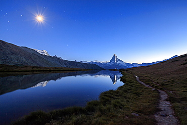 Full moon and Matterhorn illuminated for the 150th anniversary of the first ascent, reflected in Lake Stellisee, Zermatt, Canton of Valais, Swiss Alps, Switzerland, Europe