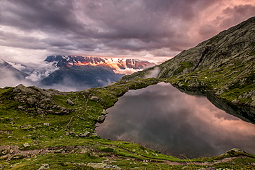 Clouds are tinged with purple at sunset at Lac de Cheserys, Chamonix, Haute Savoie, French Alps, France, Europe