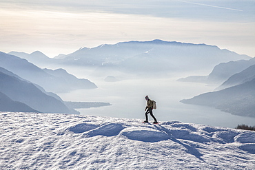 Winter view of Lake Como while a hiker proceeds with snowshoes, Vercana mountains, High Lario, Lombardy, Italy, Europe