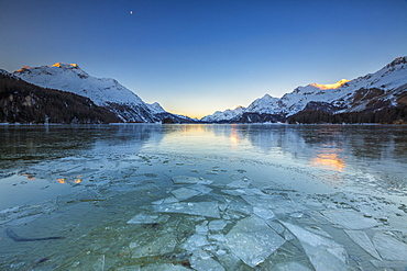 Sheets of ice on the surface of Lake Sils in a cold winter morning at dawn, Engadine, Canton of Graubunden, Switzerland, Europe