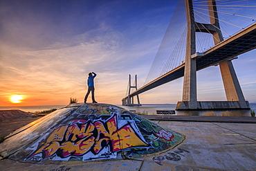 A tourist admires the majestic Vasco da Gama Bridge over the River Tagus, Parque das Nacoes, Lisbon, Portugal, Europe