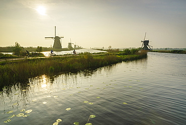 Bicycles run through a path between the canal and windmills, Kinderdijk, Rotterdam, South Holland, Netherlands, Europe