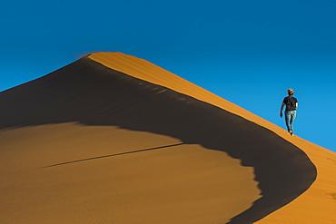 Woman hiking up the giant Sand Dune 45, Sossusvlei, Namib-Naukluft National Park, Namibia, Africa