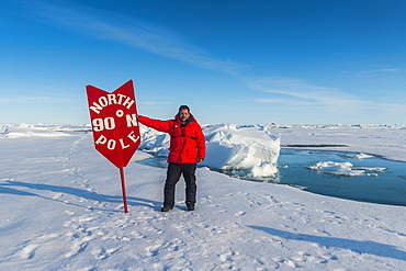 Man standing by sign at North Pole, Arctic