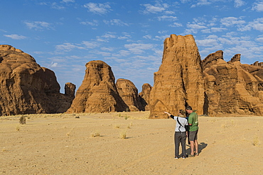 Couple looking at beautiful rock formations, Ennedi Plateau, UNESCO World Heritage Site, Ennedi region, Chad, Africa