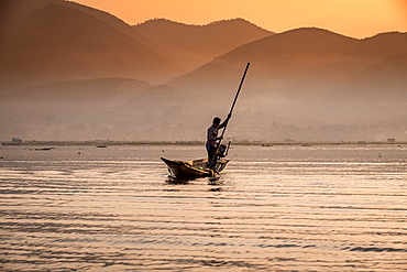 Young fisherman with net at sunrise, Inle Lake, Shan state, Myanmar (Burma), Asia