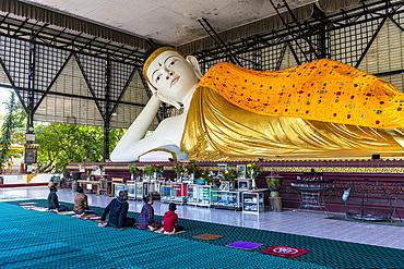 Pilgrims praying before a reclining Buddha, Su Taung Pyi pagoda, Myitkyina, Kachin state, Myanmar (Burma), Asia