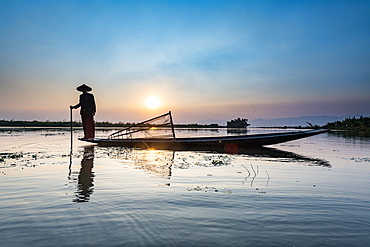 Fisherman at Inle Lake with traditional Intha conical net at sunset, fishing net, leg rowing style, Intha people, Inle Lake, Shan state, Myanmar (Burma), Asia