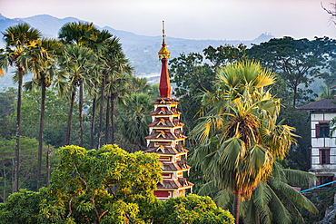 Top of a pagoda rises out of the forest, Kyaikthanian paya, Mawlamyine, Mon state, Myanmar (Burma), Asia