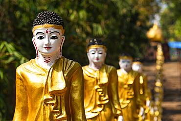 Long line of golden Buddhas lining up to Shwemawdaw Paya, Kyaing Ywar near Ye, Mon state, Myanmar (Burma), Asia