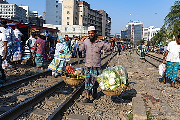 Street vendor on the railway tracks going through Kawran Bazaar, Dhaka, Bangladesh, Asia
