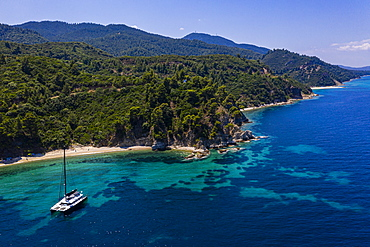 Aerial by drone of a sailing boat on Zografou Beach, Sithonia, Greece, Europe