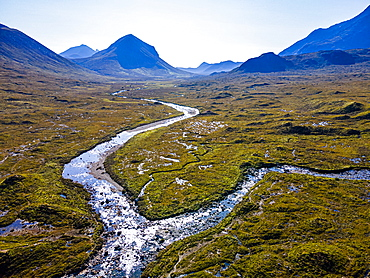 Aerial of a river snaking through the moor of the Black Cuillin ridge, Isle of Skye, Inner Hebrides, Scotland, United Kingdom, Europe