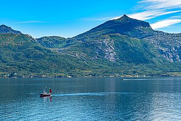 Little boat before the rugged mountain scenery, Kystriksveien Coastal Road, Norway