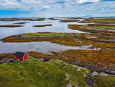 Aerial of a red boat shed on the rugged coastline of the Unesco world heritage site, the Vega Archipelago, Norway