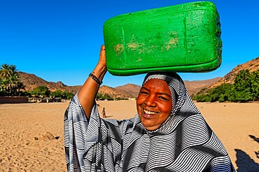 Woman carrying a water container on her head, Oasis of Timia, Air Mountains, Niger, Africa