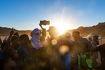 Backlight of a crowd of children and Tuareg men, Oasis of Timia, Air Mountains, Niger, Africa