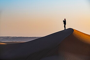 Man hiking through the sand dunes, Dirkou, Djado Plateau, Sahara, Niger, Africa