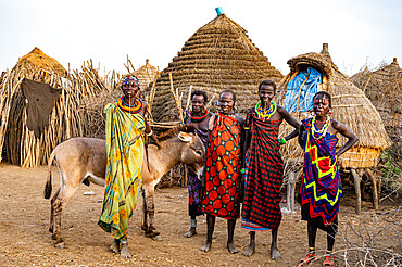 Women with a donkey in front of their hut, Jiye tribe, Eastern Equatoria State, South Sudan, Africa