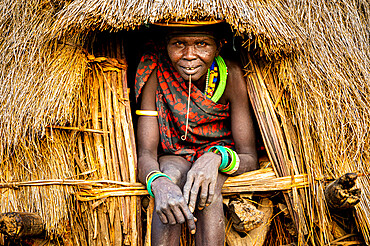 Scar face as a mark of beauty on woman from the Jiye tribe sitting in her hut, Eastern Equatoria State, South Sudan, Africa