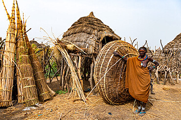 Woman in front of her hut with ready prepared reeds, Jiye tribe, Eastern Equatoria State, South Sudan, Africa