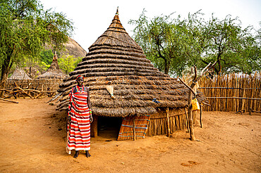 Young women in front of a traditional village hut of the Laarim tribe, Boya Hills, Eastern Equatoria, South Sudan, Africa
