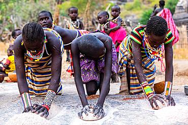 Young girls grinding Sorghum on a rock, Laarim tribe, Boya Hills, Eastern Equatoria, South Sudan, Africa