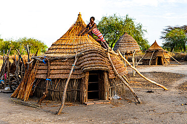 Woman repairing a roof of a traditional hut of the Toposa tribe, Eastern Equatoria, South Sudan, Africa