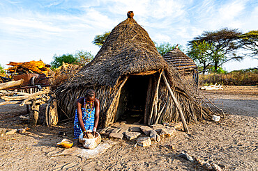 Woman grinding Sorghum in front of a traditional hut of the Toposa tribe, Eastern Equatoria, South Sudan, Africa
