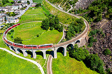 Aerial of a Train crossing the Brusio spiral viaduct, UNESCO World Heritage Site, Rhaetian Railway, Switzerland, Europe