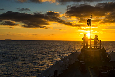 Tourists standing on the bow of a cruise ship watching the sunset, South Orkney Islands, Antarctica, Polar Regions