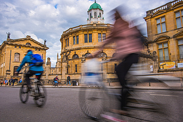 Cyclists passing the Sheldonian Theatre, Oxford, Oxfordshire, England, United Kingdom, Europe