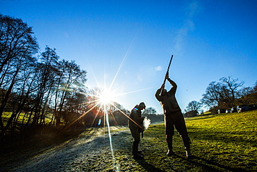 Game-shooters on a blue sky day with sun star, Norfolk, England, United Kingdom, Europe