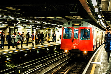 Tube pulling in to a busy underground station, London, England, United Kingdom, Europe