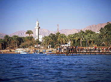 Youths swimming from jetty, town beach, Aqaba, Jordan, Middle East