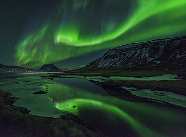 Aurora borealis (Northern Lights) reflected in partially frozen lake, North Snaefellsnes, Iceland, Polar Regions