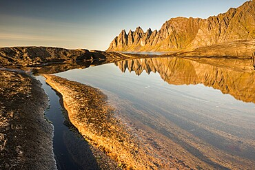 Reflection in rock pool of Devil's Teeth Mountains, from Tungenet, evening sunlight, Senja, Norway, Scandinavia, Europe
