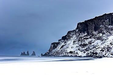 Black basalt sea stacks and snow covered black sand beach, Vik, Iceland, Polar Regions