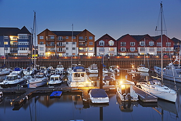 A dusk view of modern harbourside housing, beside the estuary of the River Exe, at Exmouth, Devon, England, United Kingdom, Europe