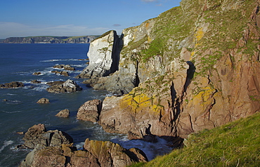 A rocky shoreline in calm summer weather, on Burgh Island, near Bigbury-on-Sea, the south coast of Devon, England, United Kingdom, Europe
