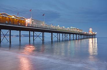 A dusk view of a classic seaside pier, Paignton Pier, Torbay, Devon, England, United Kingdom, Europe